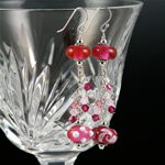 Top bead is Cranberry Pink over clear; bottom beads are Cranberry Pink over a base of white and decorated with white stringer