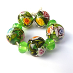 This set of garden beads has a lot of #loriandkim flower murrini on a base of Eclectus Parrot and features leaf cane made with Eden over Effetre Pea Green.